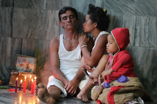 A family rests after traveling across Cuba to attend the procession for St. Lazarus.